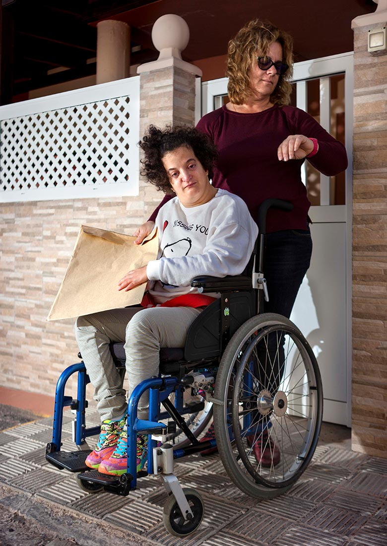 Persona con discapacidad esperando con su madre el transporte que no llega.
